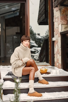 Close-up portrait of woman in white sweater, sitting by home on a terrace