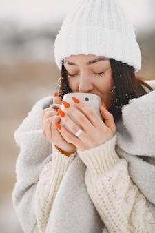 Ritratto del primo piano della donna in maglione bianco con tè