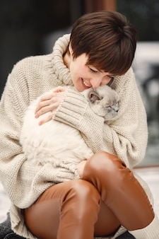 Close-up portrait of woman in white sweater with white cat