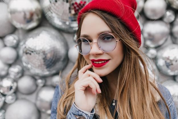 Ritratto del primo piano della ragazza meravigliosa con trucco luminoso che posa sulla parete della scintilla. la foto del modello femminile estatico indossa cappello rosso e occhiali blu rotondi.