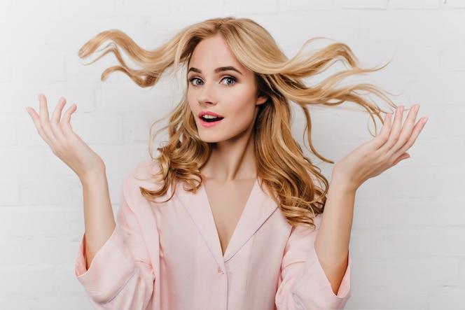 Il ritratto del primo piano della signora meravigliosa gioca con i suoi lunghi capelli biondi. foto dell'interno della splendida modella europea in pigiama rosa isolato sul muro bianco.