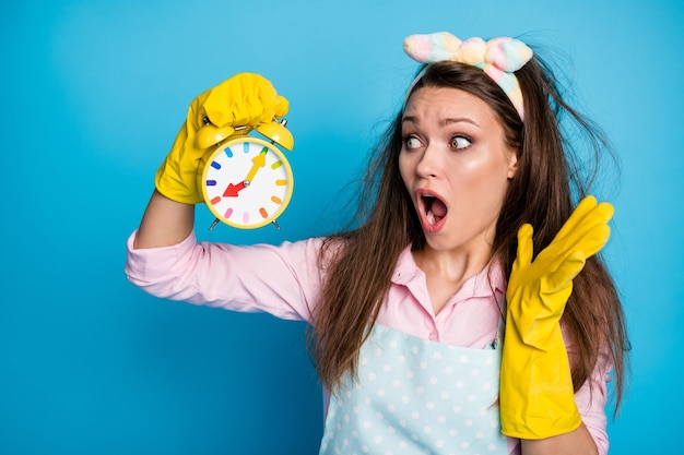Close-up portrait of worried desperate maid holding in hand clock over sleep