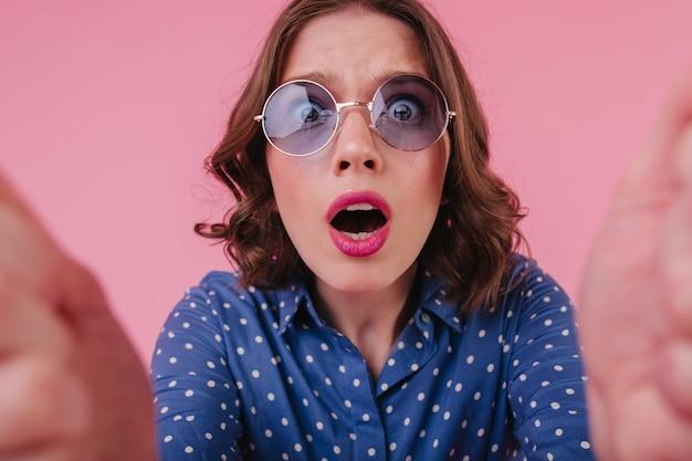 Ritratto del primo piano della donna preoccupata in camicia blu. foto di una ragazza dai capelli corti con gli occhiali che fanno selfie sulla parete rosa.
