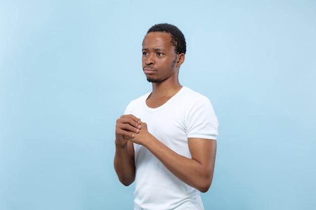 Vicino ritratto di giovane modello maschio afro-americano in camicia bianca .. dubbi, chiedendo, mostrando incertezza, riflessivo.