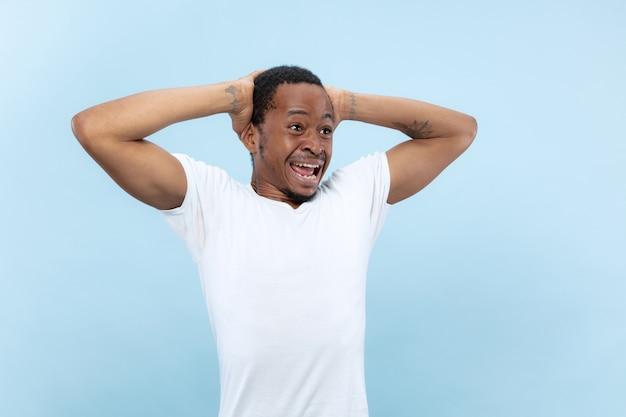 Vicino ritratto di giovane modello maschio afro-americano in camicia bianca. emozioni umane, espressione facciale, pubblicità o concetto di scommesse. scioccato, eccitato, stupito.