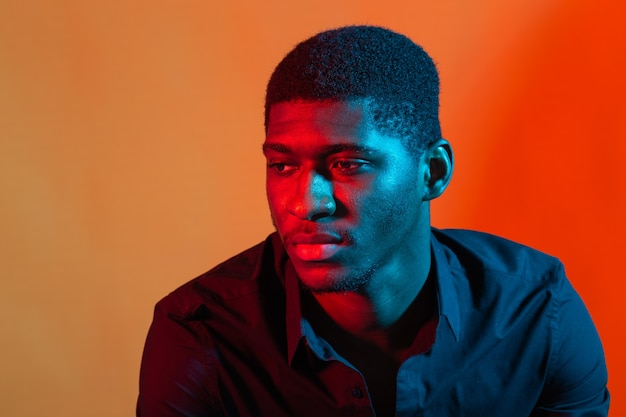 Close up portrait of a young african american man on orange neon wall.
