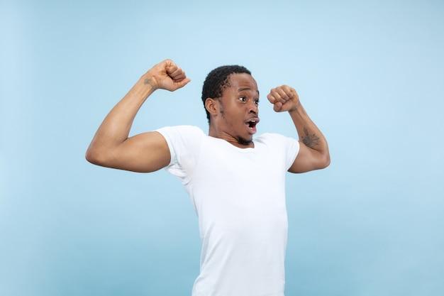Vicino ritratto di giovane uomo afro-americano in camicia bianca. emozioni umane, espressione facciale, annuncio, concetto. celebrando, meravigliato, stupito, scioccato, pazzo felice.