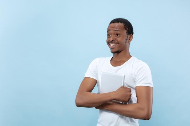 Vicino ritratto di giovane uomo afro-americano in camicia bianca. emozioni umane, espressione facciale, annuncio, concetto di vendita. tenendo una tavoletta e sorridendo. sembra felice.