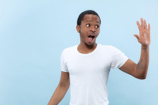 Vicino ritratto di giovane uomo afro-americano in camicia bianca. emozioni umane, espressione facciale, annuncio, concetto di vendita. incontrare qualcuno, salutare, invitare.