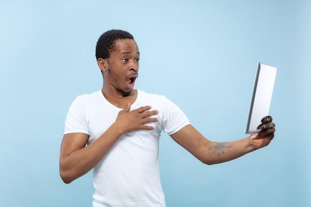 Vicino ritratto di giovane uomo afro-americano in camicia bianca. emozioni umane, espressione facciale, annuncio, concetto di vendita. utilizzando tablet, scioccato. fare selfie o vlog.
