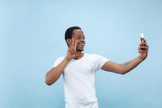 Vicino ritratto di giovane uomo afro-americano in camicia bianca .. fare selfie o contenuti per i social media, vlog.