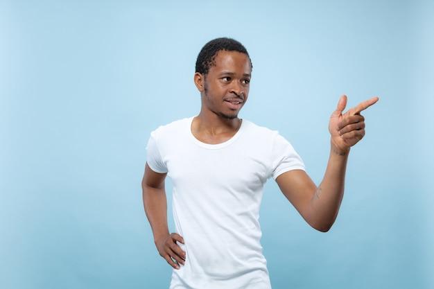 Vicino ritratto di giovane uomo afro-americano in camicia bianca .. indicando, scegliendo e sorridente.