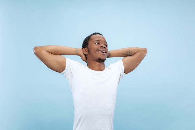 Vicino ritratto di giovane uomo afro-americano in camicia bianca .. rilassante e guarda felice, sorridente, agghiacciante.