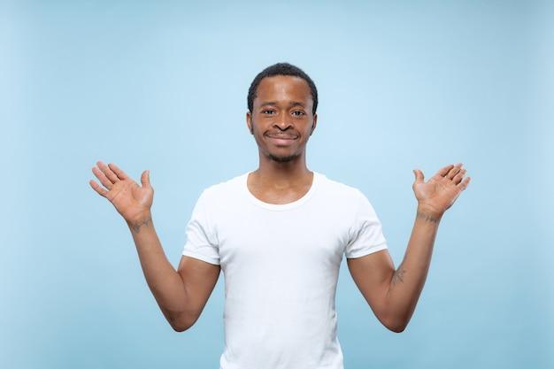 Vicino ritratto di giovane uomo afro-americano in camicia bianca .. mostrando barra vuota, indicando, scegliendo, invitando.
