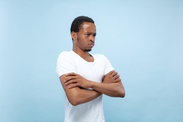 Vicino ritratto di giovane uomo afro-americano in camicia bianca. mani in piedi incrociate e tristi, sconvolte o calme.