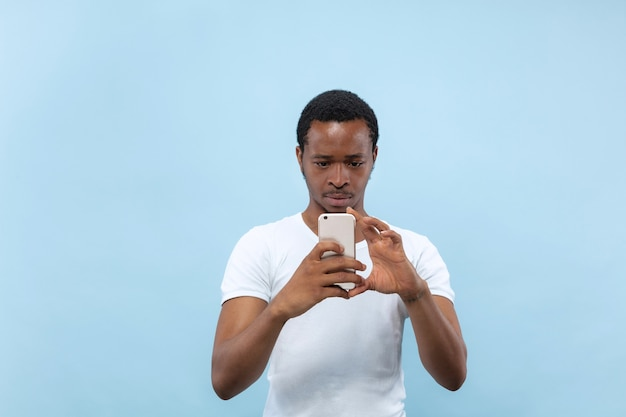 Vicino ritratto di giovane uomo afro-americano in camicia bianca ... scattare una foto o un contenuto vlog sul suo smartphone.