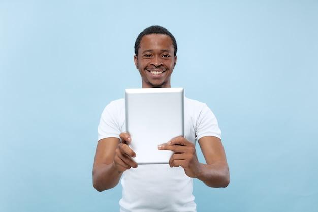 Vicino ritratto di giovane uomo afro-americano in camicia bianca. utilizzo di tablet per selfie, vlog, parlare.