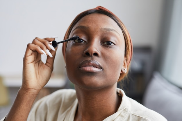 Close up portrait of young african-american woman doing makeup at home in morning and looking at camera while putting on mascara