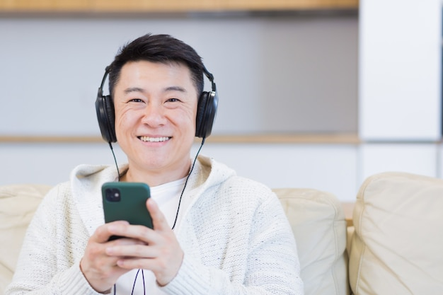 Close up portrait of young asian man listening to music online in headphones using cellphone