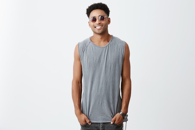 Close up portrait of young athletic dark skinned african male with curly hair in grey sporty shirt and sun glasses holding hands in pockets, looking in camera with relaxed and happy face expression
