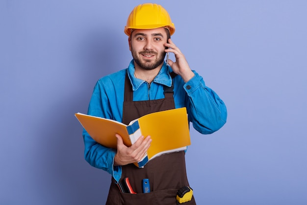 Close up portrait of young attractive bearded builder having conversation via phone and holding paper folder in hands, dresses blue shirt, brown apron, yellow helmet. buildingand engineering concept.