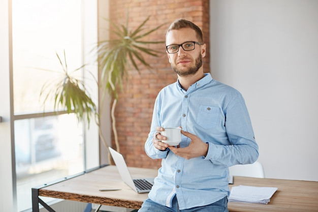 Close up portrait of young attractive company founder in glasses and casual outfit, standing in personal office