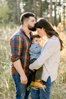 Close up portrait of young attractive family with little baby son, posing in beautiful autumn pine forest at sunny day
