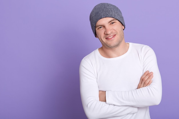 Close up portrait of young attractive man wearing white casual long sleeve shirt and gray cap, posing isolated on lilac, standing with folded arms. copy space.