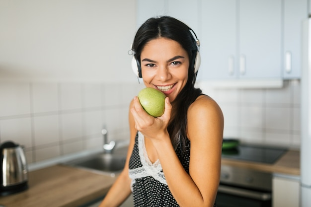 Close up portrait of young attractive woman cooking in kitchen in morning, eating apple, smiling, happy positive housewife, healthy lifestyle, listening to music on headphones, laughing, white teeth