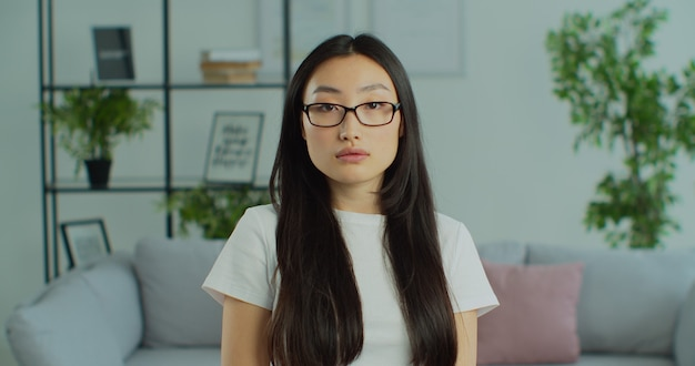 Close up portrait of young beautiful asian woman in glasses at home