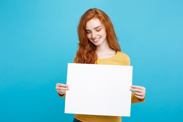 가 까이 서 세로 젊은 아름 다운 매력적인 생강 빨간 머리 소녀 빈 기호 표시 웃 고. 블루 파스텔 배경입니다. 공간을 복사하십시오.