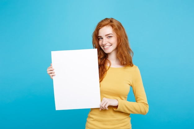 Close up portrait young beautiful attractive ginger red hair girl smiling showing blank sign blue pastel wall copy space