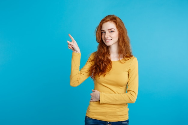 Close up portrait young beautiful attractive redhair girl happy with something and pointing finger. blue pastel background. copy space.