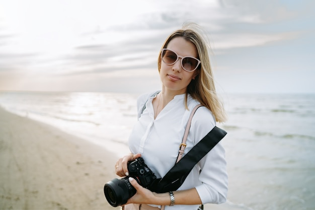 Close up portrait of young beautiful blond woman holding professional camera on the coast