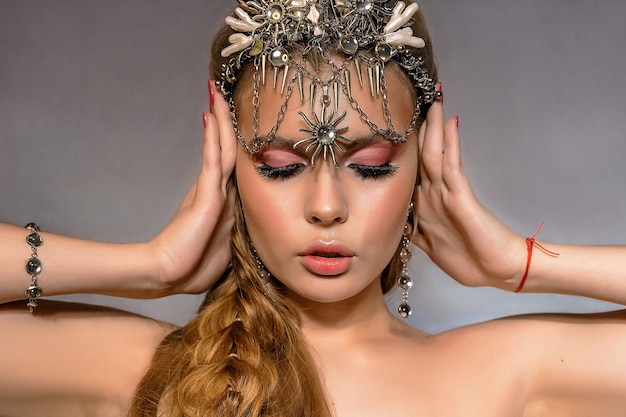 Close up portrait of a young beautiful blonde woman wearing a crown and costume jewelry on a gray background.