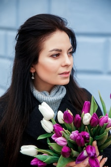 Close-up portrait of young beautiful brunette woman with tulips in city street
