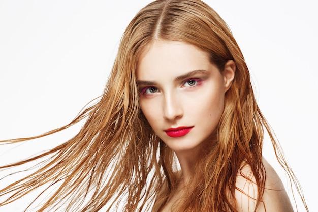 Ritratto del primo piano di giovane bella ragazza sicura con i capelli di volo e trucco luminoso. muro bianco. isolato.