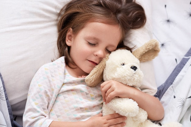 Close up portrait of young beautiful darkhaired girl, little princess with long hair, keeps eyes closed, child lies in bed, sleeping in linen with dondelion