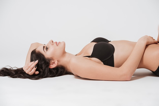 Close up portrait of a young beautiful woman in black lingerie laying on her back isolated