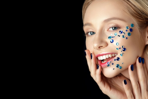 Close up portrait of young beautiful woman with blue rhinestones her face over black background.