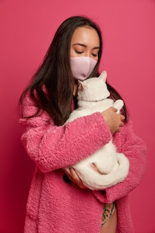 Close up portrait of young beautiful woman with protective mask holding a cat isolated