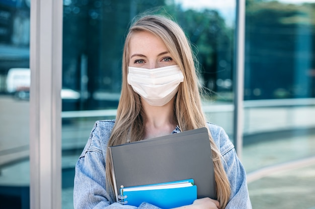Close up portrait of a young blonde girl in a medical mask