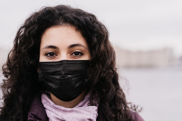 Close up portrait of a young brunette woman with big brown eyes in the medicine mask on her face thinking about virus.