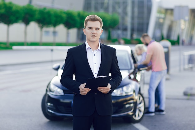 Close-up portrait of a young car dealer in a business suit. behind him, a young couple, a man and a woman inspect a new car. purchase of machines, test drive.