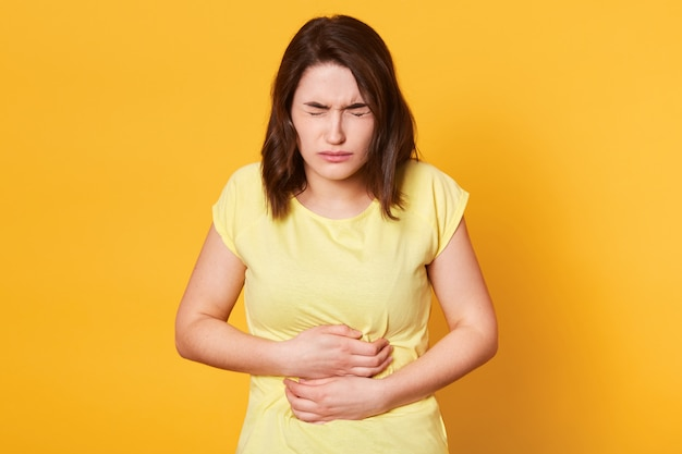 Close up portrait of young caucasian woman with awful stomachache on yellow, eats something expired, has intoxication