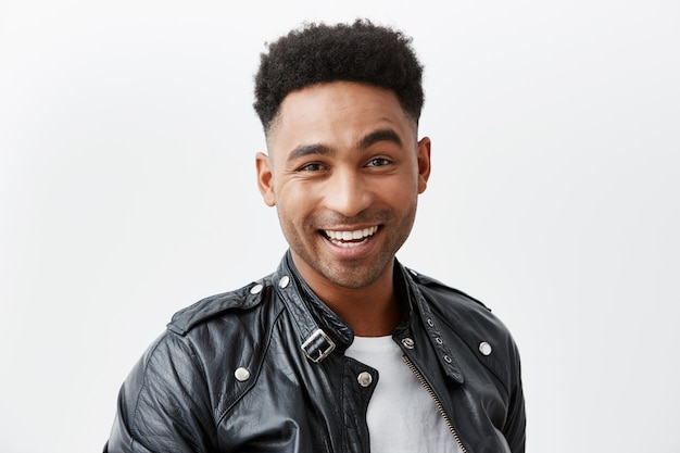 Close up portrait of young cheerful dark-skinned american man with curly hair in white t-shirt and leather jacket smiling brightly, looking in camera with happy and excited face expression.