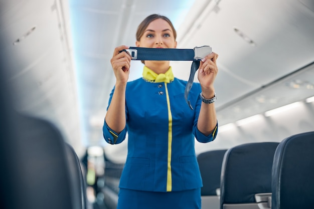 Close up portrait of young cheerful flight attendant in blue business uniform demonstrating how fostering passenger seatbelt