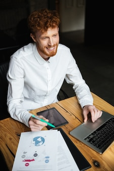 Close-up portrait of young cheerful redhead curly business man in white shirt working on laptop, looking aside