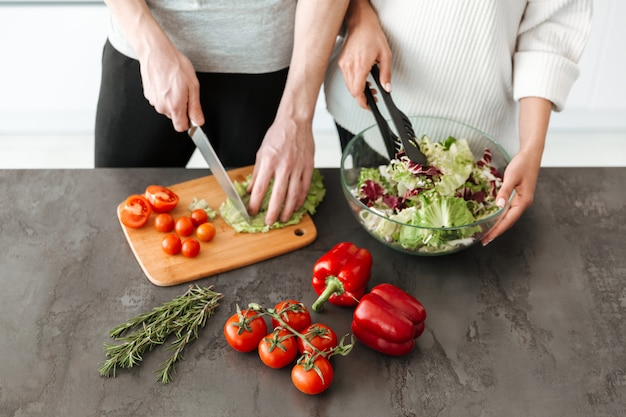Close up portrait of a young couple cooking salad