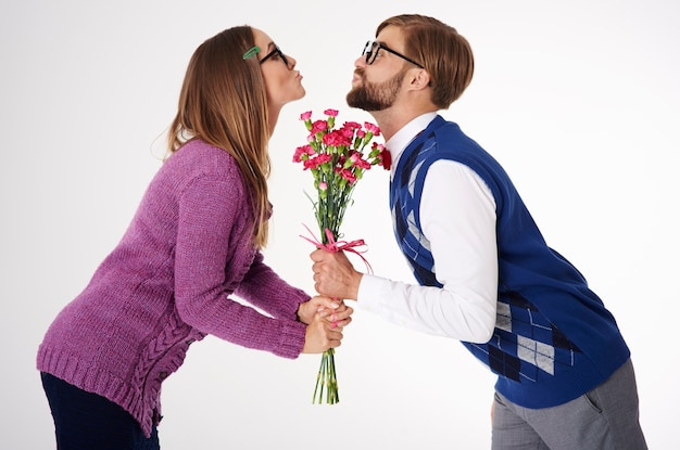 Close up portrait of young couple kissing over flowers